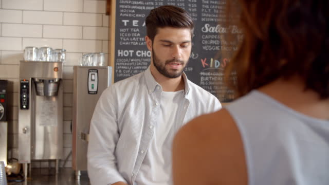 Barista taking card payment from a customer at a coffee shop video