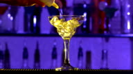 Barman making cocktail in a glass using ice and alcohol liquid, on bar, slow motion video