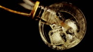 barman pouring whiskey with ice cubes in the glass on wood table, view top video