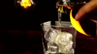 barman pouring whiskey with ice cubes on wood table, warm atmosphere, time of relax with whisky with some light warm vintage bulb video