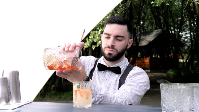 barman pours out mixing glass into prepared wine glass with liqueur, bar worker preparing cocktail video