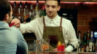 Barman preparing cocktail for a client and waiting for his reaction video