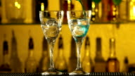 Barman puts cubes of ice into a glass, pouring different alcohol liquids, turquoise, using gayser, two glasses bar, spatter, slow motion video