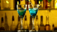 Barman puts cubes of ice into a glass, pouring three different alcohol liquids, turquoise, using gayser, two glasses, bar, spatter, slow motion video