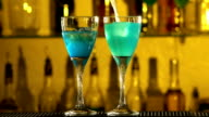 Barman puts cubes of ice into a glass, pouring three different alcohol liquids, turquoise, also pinapple juice, using gayser bar, two glasses, spatter, slow motion video
