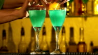 Barman puts cubes of ice into a glass, pouring three different alcohol liquids, turquoise, using gayser, two glasses, decorates with slice of orange and cherry, bar, spatter, slow motion video