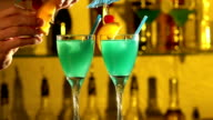 Barman puts cubes of ice into a glass, pouring three different alcohol liquids, turquoise, using gayser, two glasses, decorates with slice of orange and cherry, tubules, bar, spatter, slow motion video