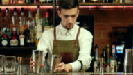Barman shaking cocktail and pouring it to an empty glass at a nightclub video