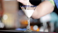 Bartender filling martini glass with bailey's irish cream video