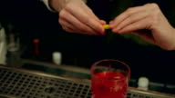 Bartender hand finish the cocktail, decorating it with slice of orange video