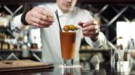 Bartender in hat is preparing cocktail in bar video