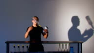 Bartender juggles glass and bottle. Medium shot video