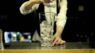 Bartender mixes up the ice in a glass video