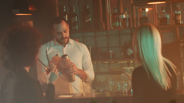 Bartender mixing and pouring drink 4K video
