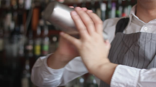 Bartender mixing coctail in shaker video