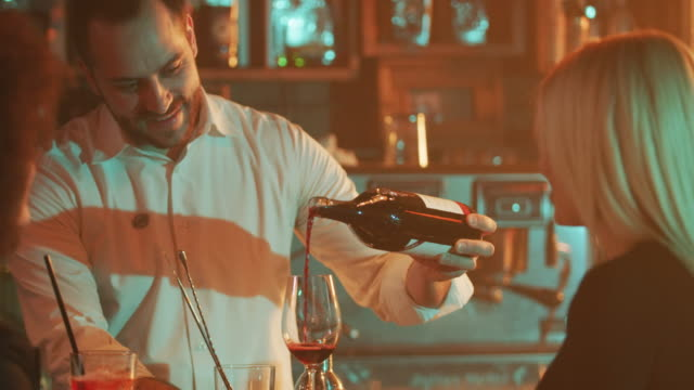 Bartender pouring red wine 4K video