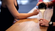 Bartender pours in protein for ladies behind the bar fitness bar video