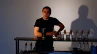 Bartender pours juggler in glass alcohol. Medium shot video