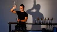 Bartender pours juggler in shaker alcohol. Medium shot video