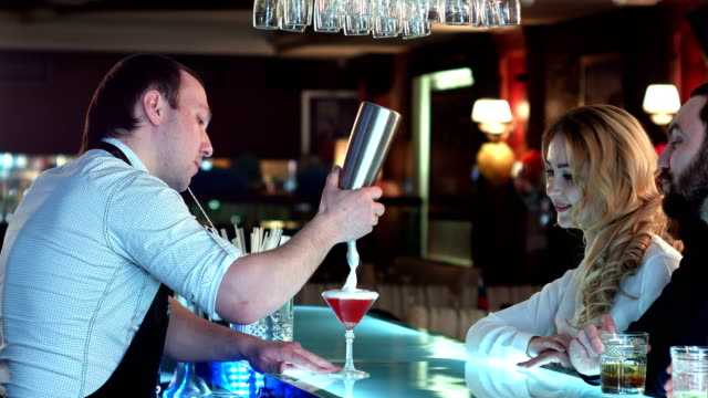 Bartender preparing cocktail for a girl who is looking forward to sitting at the bar video