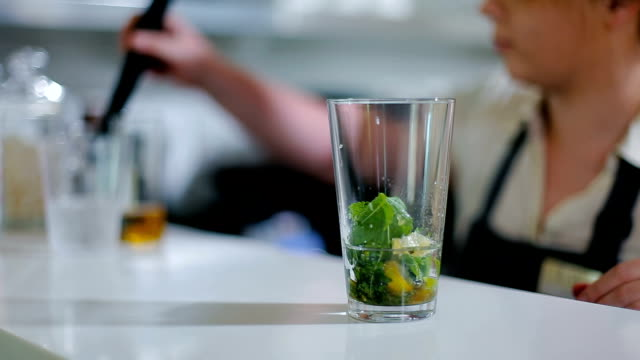 Bartender presses fresh mint leaves in a glass. video