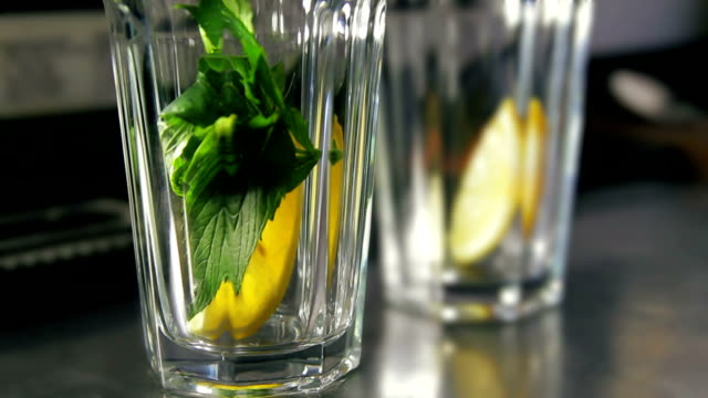 Bartender strewing lemon, mint and lots of ice into glasses video