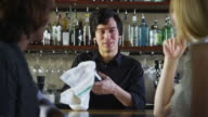 Bartender talks to customers and serves drinks video