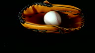 Baseball glove and ball on a black background, slow motion video