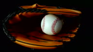 Baseball glove and ball on a black background video