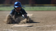 Baseball player slides into base, slow motion video
