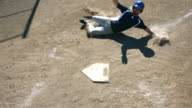 Baseball player slides into home base, slow motion video