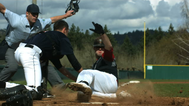 Baseball player slides is safe at home plate, slow motion video