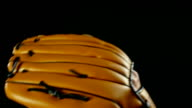 Baseball player with glove and ball on a black background, slow motion video