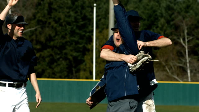 Baseball players and coach celebrate victory, slow motion video