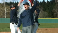 Baseball players pour cooler of water over coach, slow motion video