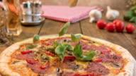 SLO MO Basil leaves falling onto mushroom and salami pizza video