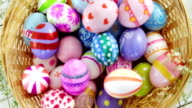 Basket with painted Easter eggs on wooden surface video
