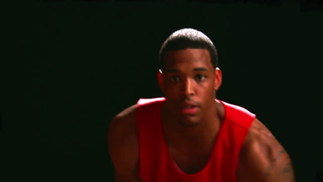 A basketball player dribbles the ball low to the gound against a black backdrop, close up video