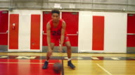 Basketball player dribbling the ball through his legs, toward the camera video