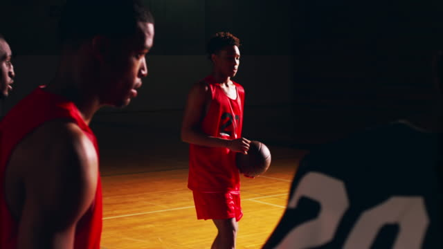 A basketball player shooting a free throw, slow motion, dark video