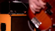 Bassist. Defocus from amplifier & speaker box in background to close-up on a male hand playing bass. video