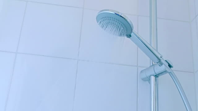 bathroom hand shower with water stream, on the white tiles video