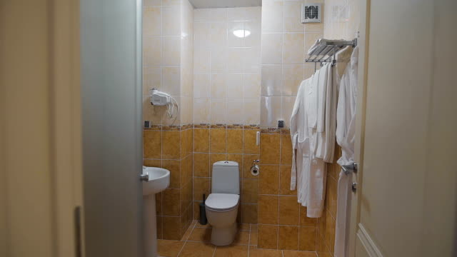 Bathroom with sink, toilet, mirror and white towels and bathrobes that hang on a hanger. Room in which there is everything you need to freshen up video