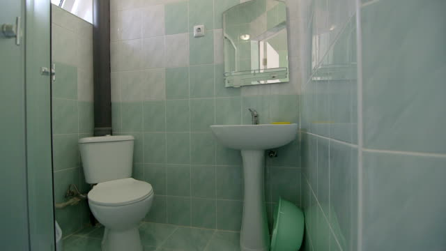 Bathroom with toilet sink and shower in cheap budget hotel room video