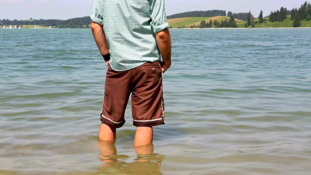 Bavarian cools his feet in a lake video