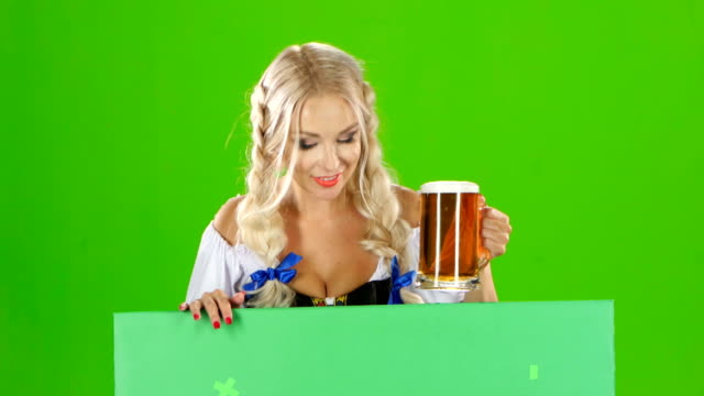 Bavarian girl looks out from behind a with a glass of beer and winking . Green screen video