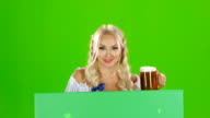 Bavarian girl looks out from behind a with a glass of beer and showing thumbs up. Green screen video