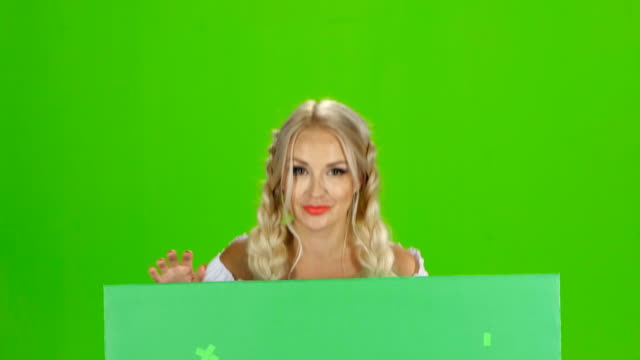 Bavarian girl looks out from behind the green board and winking. Green screen video