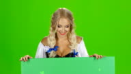 Bavarian girl looks out from behind the green board. Green screen video
