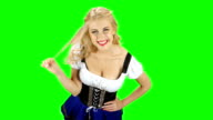 Bavarian woman flirty winds to finger a strand of hair and smiling. Green screen video